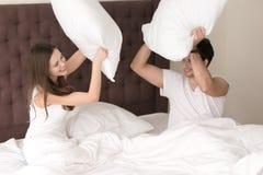 Muchacha alegre e individuo que luchan con las almohadas que se sientan en cama Fotos de archivo libres de regalías