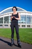 Muchacha alegre en música que escucha de los pcteres de ruedas en parque Foto de archivo libre de regalías