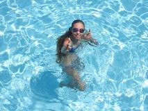 Muchacha alegre en piscina que sonríe y que muestra los pulgares para arriba fotos de archivo