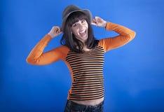 Muchacha alegre en un sombrero en un fondo azul Fotografía de archivo
