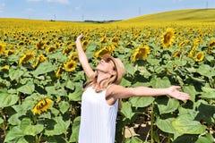 Muchacha alegre en una granja del girasol Imagenes de archivo