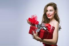 Muchacha alegre en vestido rojo con los regalos Imágenes de archivo libres de regalías