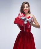 Muchacha alegre en vestido rojo con los regalos Foto de archivo libre de regalías