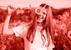 Muchacha alegre feliz con el girasol que disfruta de la naturaleza y que ríe en el campo del girasol del verano entonado en el co fotos de archivo