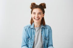 Muchacha alegre feliz joven divertida con dos bollos que ríe la sonrisa sobre el fondo blanco Fotografía de archivo libre de regalías