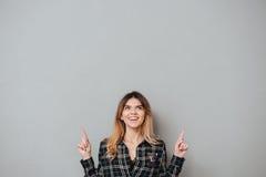 Muchacha alegre feliz que destaca dos fingeres en el espacio de la copia Imagenes de archivo