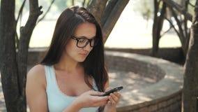 Muchacha alegre hermosa con Smartphone que se sienta en un parque en un banco en Sunny Day, concepto en línea de las compras Foto de archivo libre de regalías