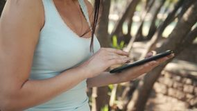Muchacha alegre hermosa con un Tablet PC que se sienta en un parque en un banco en Sunny Day, concepto en línea de las compras Foto de archivo