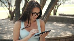 Muchacha alegre hermosa con un Tablet PC que se sienta en un parque en un banco en Sunny Day, concepto en línea de las compras Fotos de archivo libres de regalías