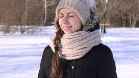 muchacha alegre hermosa 4K que bizquea en el sol y las palmadas almacen de metraje de vídeo