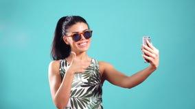 Muchacha alegre joven confiada con el pelo negro recto, actitudes en un fondo azul con smartphone en manos almacen de metraje de vídeo