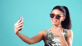 Muchacha alegre joven confiada con el pelo negro recto, actitudes en un fondo azul con smartphone en manos metrajes