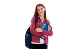 Muchacha alegre joven del estudiante con la presentación de la mochila aislada en el fondo blanco en estudio Fotografía de archivo libre de regalías