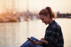Muchacha alegre joven del inconformista que se sienta en un embarcadero cerca de puerto marítimo y mensaje de texto agradable leí Foto de archivo libre de regalías