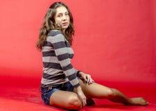 Muchacha alegre joven en pantalones cortos del dril de algodón y un suéter rayado que caminan en el estilo joven Foto de archivo libre de regalías