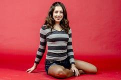Muchacha alegre joven en pantalones cortos del dril de algodón y un suéter rayado que caminan en el estilo joven Fotos de archivo libres de regalías