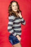 Muchacha alegre joven en pantalones cortos del dril de algodón y un suéter rayado que caminan en el estilo joven Imagen de archivo libre de regalías