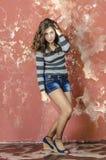 Muchacha alegre joven en pantalones cortos del dril de algodón y un suéter rayado que caminan en el estilo joven Fotografía de archivo