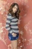 Muchacha alegre joven en pantalones cortos del dril de algodón y un suéter rayado que caminan en el estilo joven Fotos de archivo