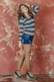 Muchacha alegre joven en pantalones cortos del dril de algodón y un suéter rayado que caminan en el estilo joven Imagen de archivo