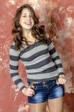 Muchacha alegre joven en pantalones cortos del dril de algodón y un suéter rayado que caminan en el estilo joven Imágenes de archivo libres de regalías