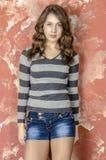 Muchacha alegre joven en pantalones cortos del dril de algodón y un suéter rayado que caminan en el estilo joven Foto de archivo