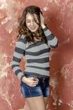 Muchacha alegre joven en pantalones cortos del dril de algodón y un suéter rayado que caminan en el estilo joven Fotografía de archivo libre de regalías