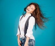 Muchacha alegre joven en un fondo azul Imagen de archivo