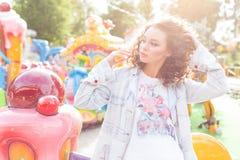 Muchacha alegre joven hermosa con el pelo rizado en pantalones cortos del dril de algodón y la camiseta blanca en un parque de at Imágenes de archivo libres de regalías