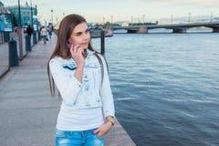 Muchacha alegre joven que llama con el teléfono de célula mientras que disfruta de g Fotografía de archivo libre de regalías
