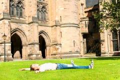 Muchacha alegre joven que miente en la hierba en Glasgow University GA Fotografía de archivo libre de regalías