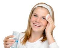 Muchacha alegre joven que quita el cojín de limpiamiento del maquillaje Imagenes de archivo