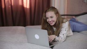 Muchacha alegre, linda joven que usa el ordenador portátil interior almacen de metraje de vídeo