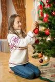 Muchacha alegre que adorna el árbol de navidad en la casa Fotos de archivo libres de regalías