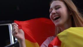 Muchacha alegre que apoya al equipo de fútbol español, besando la bandera celebrando la victoria almacen de video