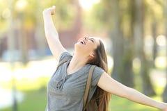 Muchacha alegre que aumenta los brazos en la calle Fotos de archivo