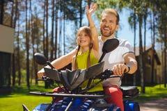 Muchacha alegre que conduce ATV con su papá Imagenes de archivo
