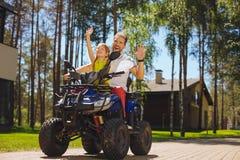 Muchacha alegre que conduce ATV con su papá Imagen de archivo