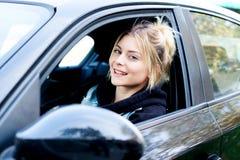 Muchacha alegre que conduce su nuevo coche listo para ir Fotos de archivo libres de regalías