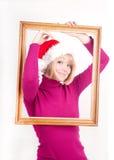 muchacha alegre que desgasta el sombrero de santa dentro del marco Fotos de archivo libres de regalías