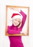 Muchacha alegre que desgasta el sombrero de santa dentro del marco Fotografía de archivo libre de regalías