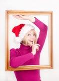 Muchacha alegre que desgasta el sombrero de santa dentro del marco Imagen de archivo