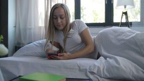 Muchacha alegre que despierta en cama y que comprueba el teléfono