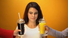 Muchacha alegre que elige soda en vez del zumo de naranja, apego a las bebidas dulces metrajes