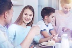 Muchacha alegre que habla para engendrar mientras que come el pedazo de torta Fotos de archivo