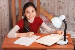 Muchacha que hace la preparación en un cuaderno Imagen de archivo