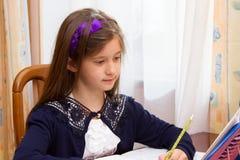 Muchacha alegre que hace la preparación en un cuaderno Imágenes de archivo libres de regalías