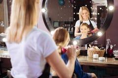 Muchacha alegre que hace su pelo cepillar en un salón de belleza Fotos de archivo libres de regalías