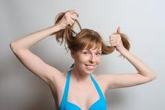Muchacha alegre que juega con el pelo Imagen de archivo libre de regalías