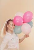 Muchacha alegre que juega con los globos coloridos Foto de archivo